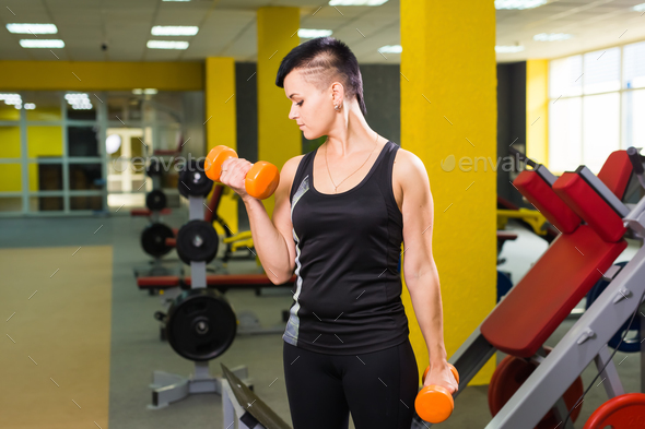 Strong fit girl exercising with dumbbells - Stock Photo - Images