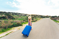 Freedom, travel, vacation and summer concept - Traveler woman walking on the road with blue suitcase