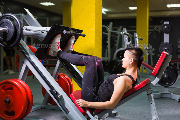 Active young woman doing exercise for legs on special equipment in gym. - Stock Photo - Images
