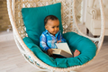Portrait of African American baby boy holding book on sofa
