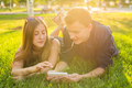 Happy couple lying on the grass and resting together, having fun outdoor. Portrait of funny lovers
