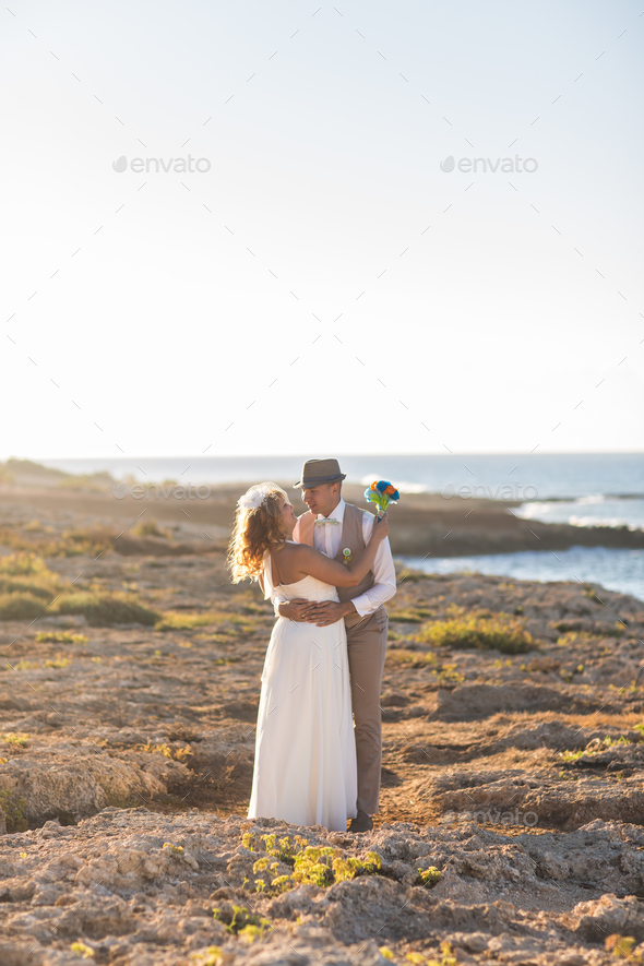Bride and groom by the sea on their wedding day. - Stock Photo - Images
