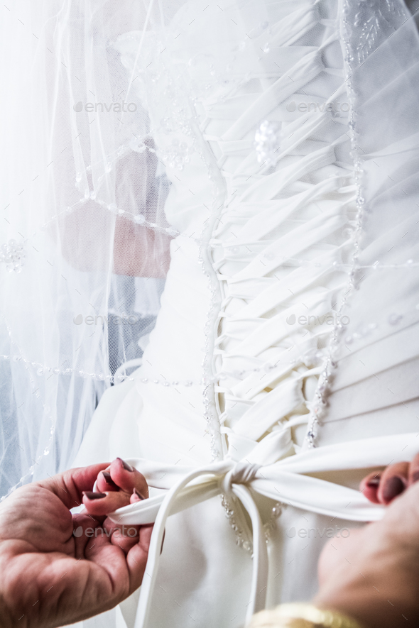 Mother Tying the Bride's Wedding dress - Stock Photo - Images