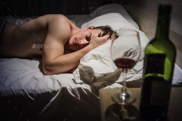 Hangover Man with Headaches in a Bed at Night - Stock Photo - Images