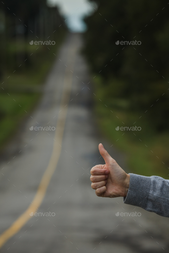 Closeup of a Thumbs up of a Caucasian Woman Hitchhiking - Stock Photo - Images
