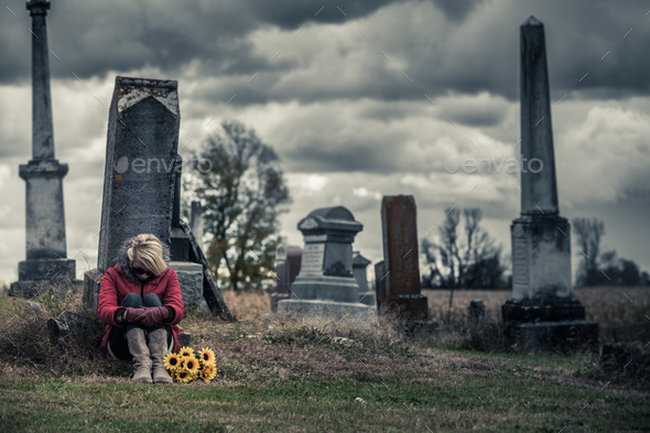 Lonely Sad Young Woman in Mourning in front of a Gravestone - Stock Photo - Images