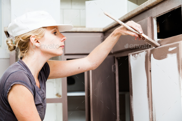 Closeup of Woman Painting Kitchen Cabinets - Stock Photo - Images