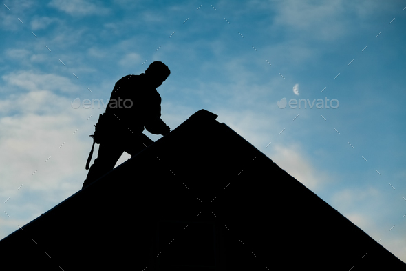 Contractor in Silhouette working on a Roof Top - Stock Photo - Images