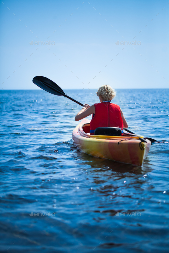 Woman Wearing a Safety Vest Heading out to sea Alone - Stock Photo - Images
