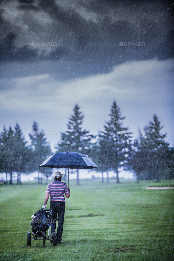 Golfer on a Rainy Day Leaving the Golf Course - Stock Photo - Images