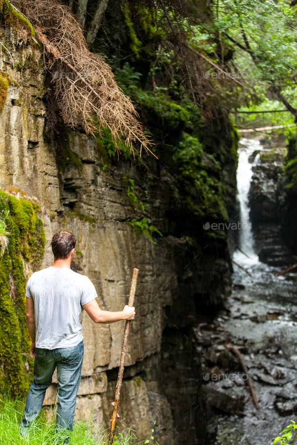 Hiker Looking at the Waterfall - Stock Photo - Images