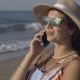 The Girl Is Talking on the Phone While Sitting on the Beach - VideoHive Item for Sale