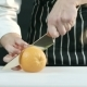 Man Cuts an Orange in Half on a Board - VideoHive Item for Sale