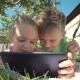 Cheerful Kids Watching Tablet in Garden - VideoHive Item for Sale