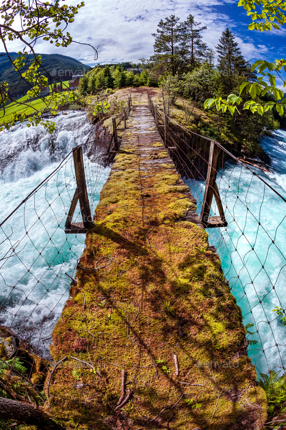 Suspension bridge over the mountain river, Norway. - Stock Photo - Images
