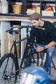 Man in cap taking measurements of bike