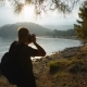 Traveler Photographer Shoots Beautiful Sunset on the Shore of a Mountain Lake - VideoHive Item for Sale