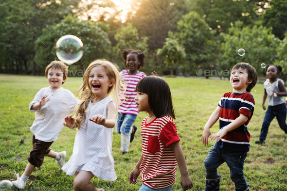 Group of Diverse Kids Playing at the Field Together - Stock Photo - Images