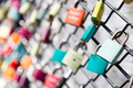 Many love padlocks on fence concept with selective focus on a blank lock at foreground
