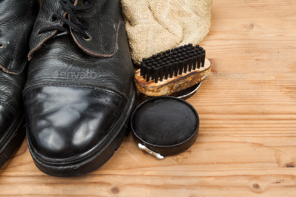 Shoe polish with brush, cloth and worn boots on wooden platform - Stock Photo - Images