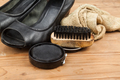 Shoe polish with brush, cloth and worn ladies court shoe on wood