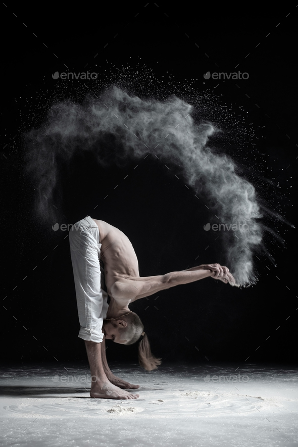 Flexible yoga man in standing forward fold uttanasana - Stock Photo - Images