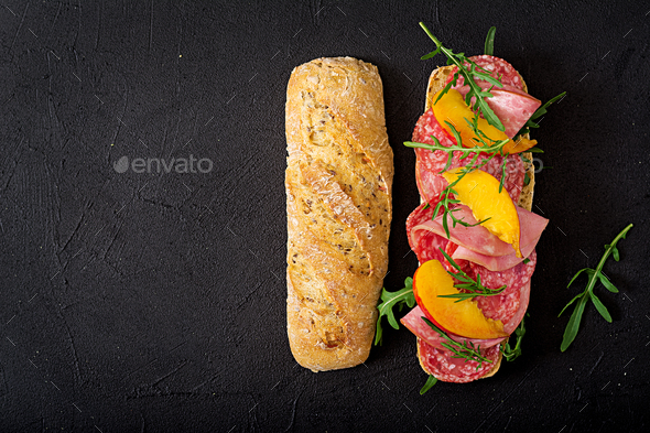 Big sandwich with ham, salami, nectarine and arugula. Flat lay. Top view - Stock Photo - Images