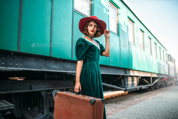 Young old-fashioned woman travels on retro train - Stock Photo - Images