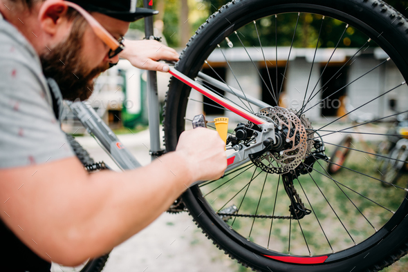 Bicycle mechanic adjusts back disk brakes - Stock Photo - Images