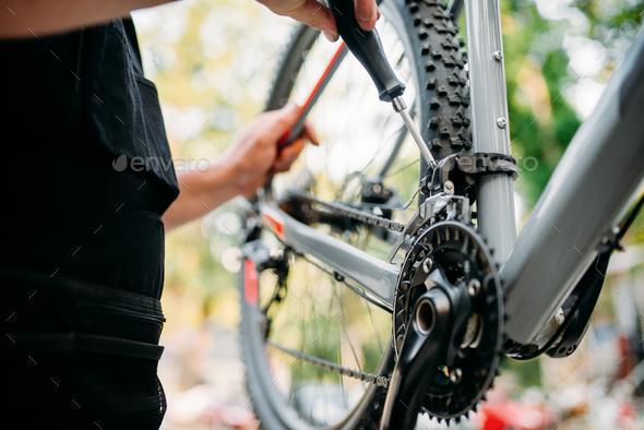 Hands with screwdriver repair shifter, bike repair - Stock Photo - Images