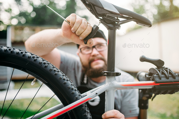 Bicycle mechanic adjusts with tools bike seat - Stock Photo - Images
