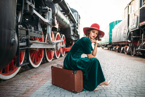 Woman in red hat against vintage steam train - Stock Photo - Images