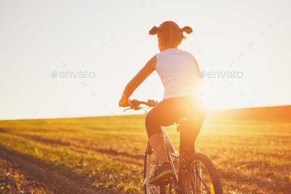 Girl enjoying bike ride at the sunset - Stock Photo - Images