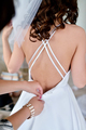 Bridesmaid is lacing white wedding dress for beautiful bride