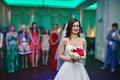 Beauty bride in bridal gown with lace veil is throwing wedding bouquet indoors