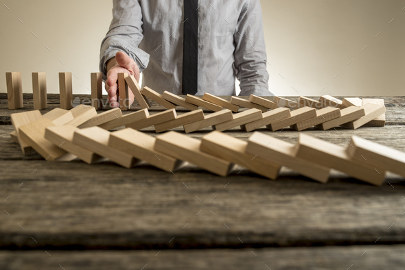 Hand stopping domino effect of wooden blocks - Stock Photo - Images