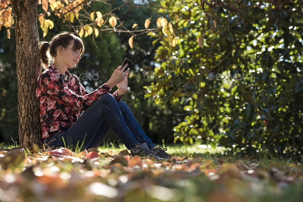 Young woman reading something on a digital device - Stock Photo - Images