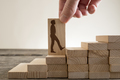 Man holding with his fingers wooden domino with shape of busines