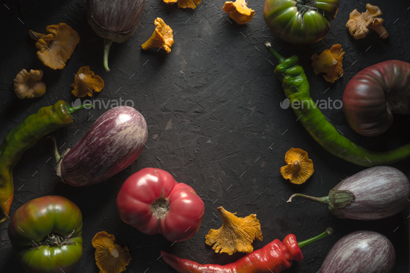 Frame of chanterelles, chili and vegetables on a gray table - Stock Photo - Images
