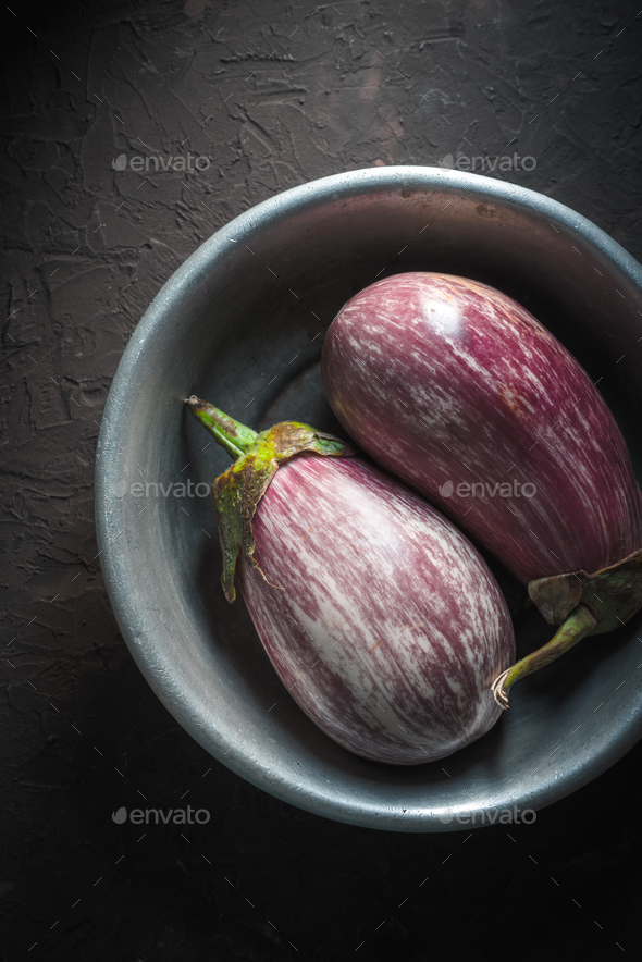 Colored eggplants in a metal bowl on a beige background in the center - Stock Photo - Images