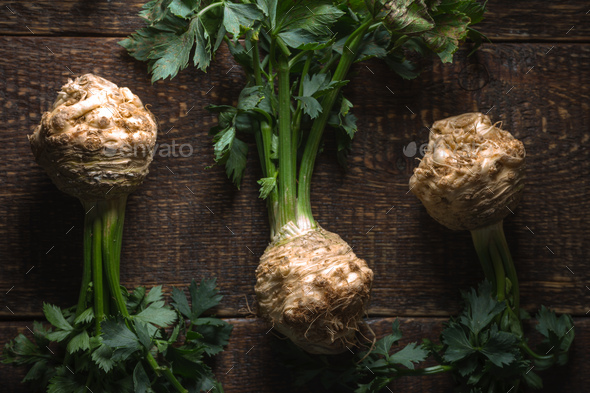 Celery roots with green leaves on brown boards - Stock Photo - Images