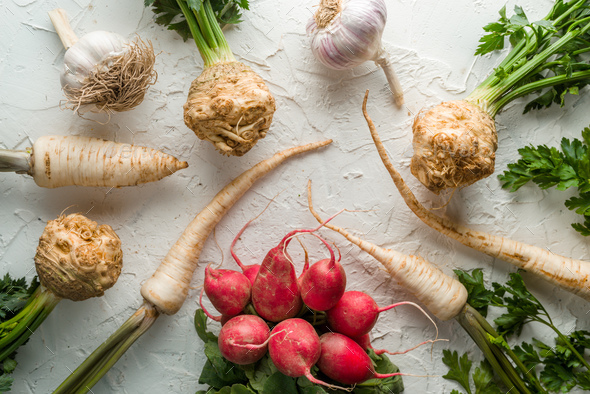 Background of celery roots, parsley, radishes with leaves and garlic on white table - Stock Photo - Images