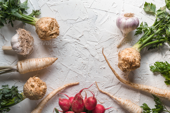 Celery roots, parsley, radishes with leaves and garlic on a white table free space - Stock Photo - Images