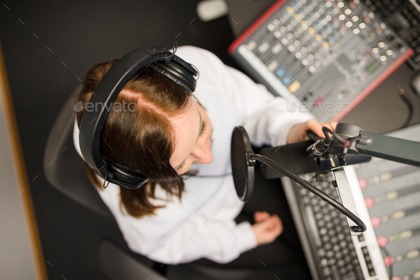 Directly Above Shot Of Radio Jockey Using Microphone And Headpho - Stock Photo - Images