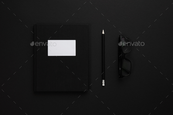 Top view of low key black office desk with notebook and glasses - Stock Photo - Images