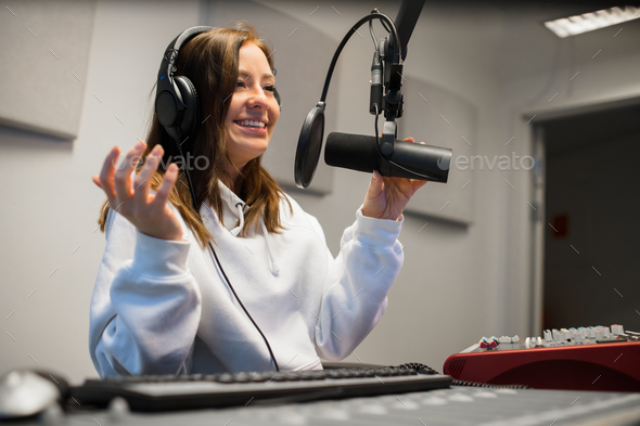 Female Jockey Communicating On Microphone In Radio Studio - Stock Photo - Images