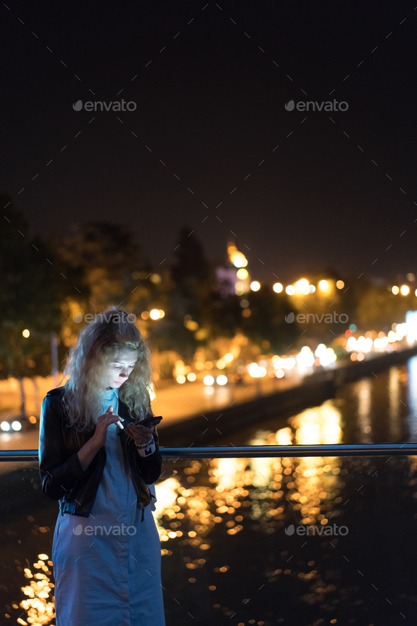 Girl with a smartphone on a bridge - Stock Photo - Images