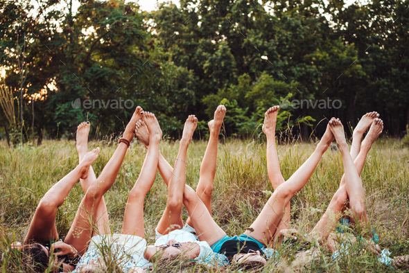 Six girls lie on the grass and raise their legs up - Stock Photo - Images
