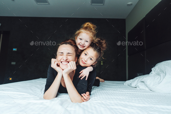 Mom and two daughters have fun on the bed - Stock Photo - Images