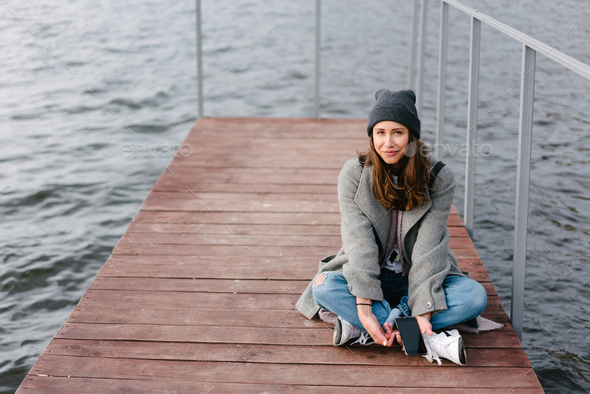 Young pretty girl on wooden bench on old pier - Stock Photo - Images